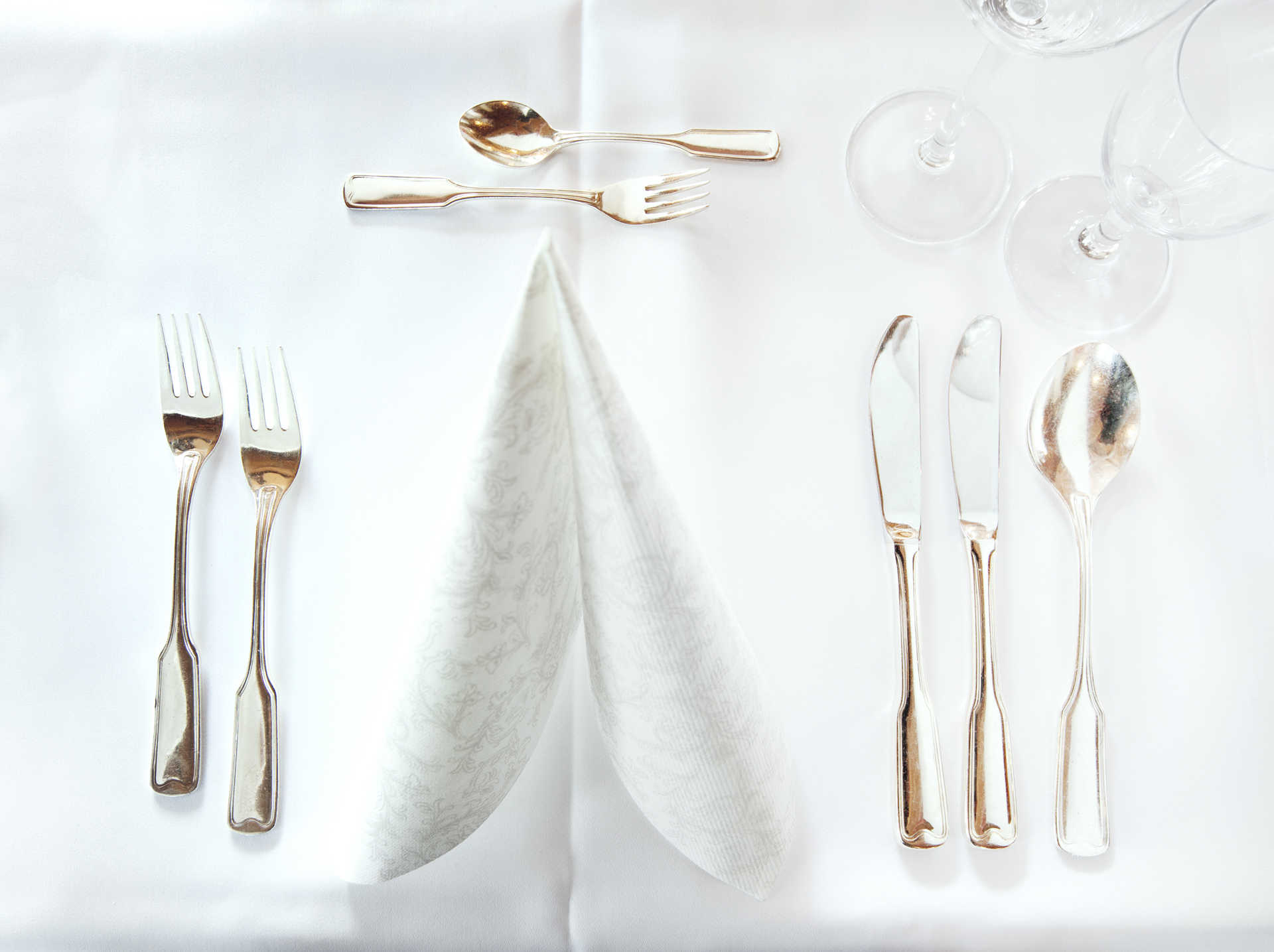 Cutlery, napkin, and wine glasses on a table